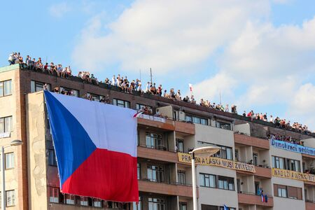 Prague, Czech Republic - June 23 2019: People on a roof of a building supporting protests against Prime Minister Babis and Minister of Justice on Letna, Letenska plan. Demonstration, czech flag. Éditoriale
