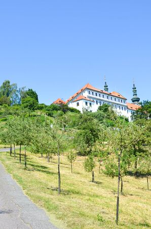 Awesome green park on Petrin Hill in the old town of beautiful Prague, Czech Republic. Old house with tower in background. Sunny day. Popular tourist spot and view point. City parks. Bohemia, Czechia.