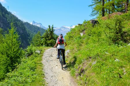 Young man riding bicycle in beautiful hilly landscape of Swiss Alps close to famous Zermatt. Outdoor sport. Bike, biker. Alpine landscape, Switzerland. Mountains with snow on top in background.