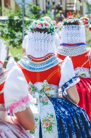 Young women during parade in traditional Czech folklore costumes. Photographed in Southern Moravia, Czechia. Moravian motifs. Festive, tradition.