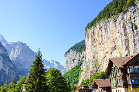 Beautiful Staubbach Falls in picturesque village Lauterbrunnen, Switzerland photographed in summer season with local chalets. Popular tourist attraction. Swiss Alps in background. Rocks.