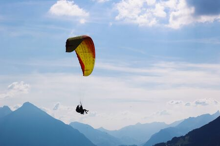 Tandem paragliding in Swiss Alps. Silhouettes of paragliders and beautiful mountains. Extreme sport, adventure sports. Adventurous lifestyle. Concept, conceptual.