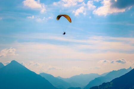 Parapentes survolant les montagnes à Interlaken, Suisse. Silhouette des Alpes suisses. Parapente biplace. L'aube, le coucher du soleil. Sports extrêmes. Mode de vie aventure. Adrénaline, concept de risque.