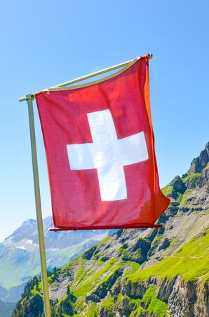 Vertical picture of Swiss waving flag with summer mountain landscape in background. National symbol. Swiss Alps. White cross on red field. National concept. Switzerland summer.