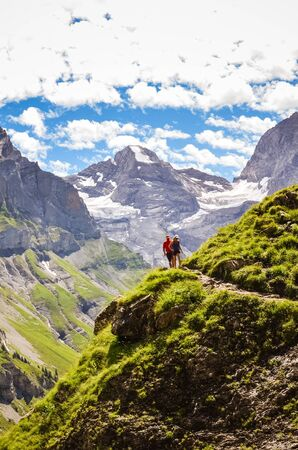 Couple walking on hiking path in the mountains captured on vertical photo. High snowcapped mountains in background. Summer adventure. Outdoor lifestyle concept. Trekking holidays.