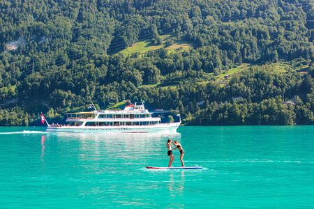 Two young girl friends standing on paddleboard on turquoise Lake Brienz in Switzerland. Tourist boat in background. Switzerland summer. Active lifestyle, sport activities. Friendship, fun.