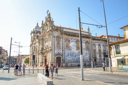 Porto, Portugal - August 31 2018: People on the street by famous Igreja do Carmo and adjacent Igreja dos Carmelitas. Traditional Portuguese tiles azulejos on church facade. Street with people.