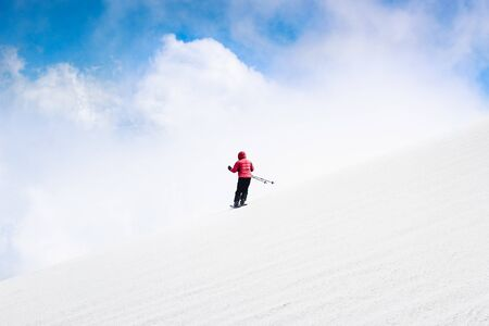Skier skiing downhill slope in red jacket. Sky and clouds behind horizon. Freeride skiing. Alpine sports, white snow. Minimalist photography. Danger, action speed concept. Banque d'images - 128383229