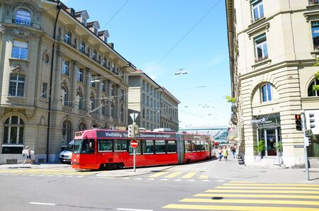 Bern, Switzerland - August 14 2019: Red tram in the city center of the Swiss capital. Red light on zebra crossing, city crossroad. Historical buildings, people walking. Sunny summer day.