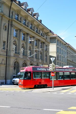 Bern, Switzerland - August 14 2019: Red tram in the city center of the Swiss capital. Red light on zebra crossing, city crossroad. Historical buildings. Sunny summer day. Editorial