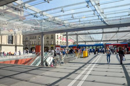 Bern, Switzerland - August 14 2019: People walking under the roof by tram station. The station is adjacent to the main train station. Tram in background. Public transport. Daily life. Swiss capital.
