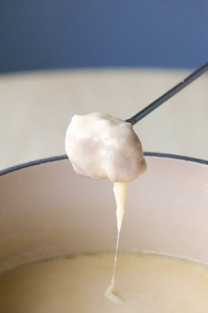 Swiss traditional dish - cheese fondue. Baguette on a fondue fork is being dipped in melted cheese. Served in a communal pot heated with a candle or spirit lamp. Close up picture. Vertical photo. Stock Photo