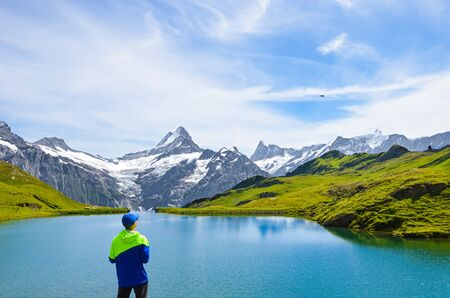 Young man operating the flying drone over beautiful Bachalpsee in the Swiss Alps. Drone cameras are used for aerial photography and footage. Switzerland landscape. Drone noise. Stockfoto