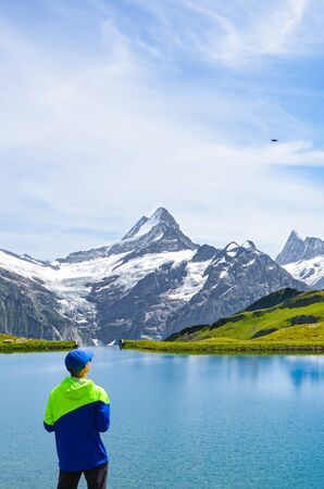 Young man operating the flying drone over amazing Bachalpsee in the Swiss Alps. Drone cameras are used for aerial photography and footage. Switzerland, Alpine landscape. Noise. Ban, forbidden.
