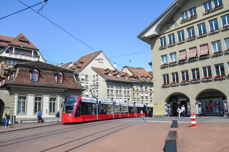 Bern, Switzerland - August 14, 2019: Red tram on the street in the city center of the Swiss capital. Public transport. Historical buildings. People on the street. Daily life.