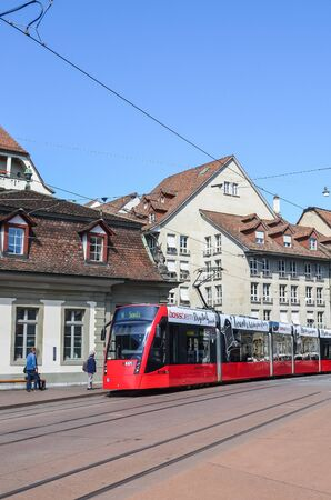 Bern, Switzerland - August 14, 2019: Red tram on the street in the city center of the Swiss capital. Public transport. Trams, transportation. Tram station. Historical buildings. People on the street. Editorial