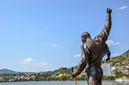 Montreux, Switzerland - July 26, 2019: Famous statue of Freddie Mercury, singer of the famous band Queen. City by Lake Geneva in background. Popular tourist attraction. Copy space, a place for text.