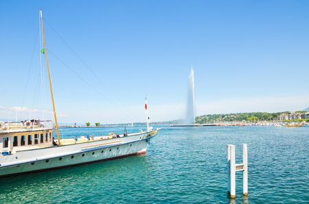 Geneva, Switzerland - July 17, 2019: Jet dEau, a famous water fountain on Geneva Lake. Symbol of the Swiss city. Famous landmark and tourist attraction photographed with tourist boat cruise. Geneve. Editorial