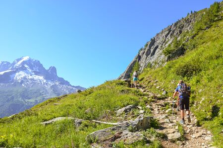 Hikers with hiking poles in French Alps near Chamonix on a trail to Lac Blanc with Mont Blanc view. Beautiful Alpine landscape in France. People with walking sticks. Alps in summer. Active vacation.