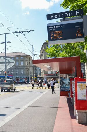 Bern, Switzerland - August 14, 2019: Bus station by the main train station in the center of the Swiss capital. Public transport. People on the street. Cars on the road. Intersection. Daily life.