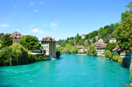 Historical buildings along turquoise Aare River in the historical center of the Swiss capital Bern. Switzerland summer, city. Sunny summer day. River bank.