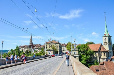 Bern, Switzerland - August 14, 2019: Historical Nydegg Bridge, Nydeggbrucke in German, in the historical center of the Swiss capital. Nydegg Church in background. People walking. Tourist attraction.