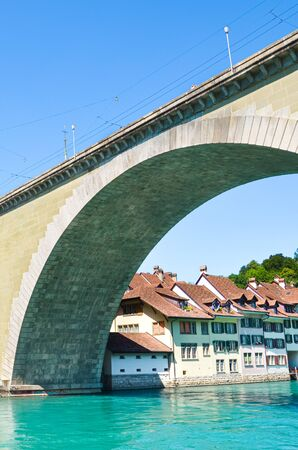 Bridge construction over turquoise Aare River in Bern, Switzerland. Photographed in summer in the Swiss capital. Historical center located along blue river. Tourist destinations.