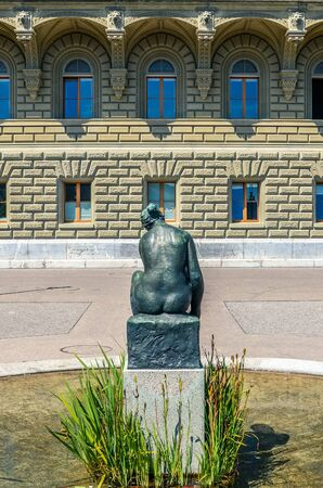 Bern, Switzerland - August 14, 2019: Statue of naked woman photographed from behind close to the Parliament Building in the Swiss capital. Woman sculpture, woman statue. Classical, art, artwork.