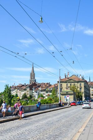 Bern, Switzerland - August 14, 2019: Historical Nydegg Bridge, Nydeggbrucke in German, in the old town of the Swiss capital. Tourists walking. Tourist attractions. Cobbled road, trolleys. Editorial