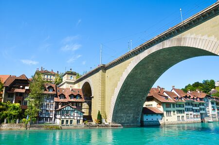 Amazing bridge construction over turquoise Aare River in Bern, Switzerland. Photographed in summer in the Swiss capital. Historical center located along the blue river. Tourist places.