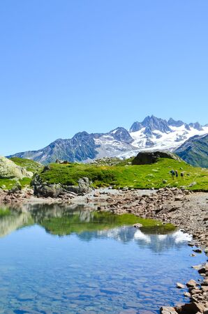 Stunning Lac de Cheserys, Lake Cheserys near Chamonix-Mont-Blanc in French Alps. Alpine lake with snow capped mountains in the background. France Alps, Tour du Mont Blanc trail. Nature background.