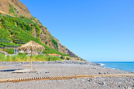 Beautiful stone beach in Madalena do Mar, Madeira, Portugal photographed in the late summer on a sunny day. Hill with banana plantations in the background. Umbrella on a beach. Madeira island. Stock fotó