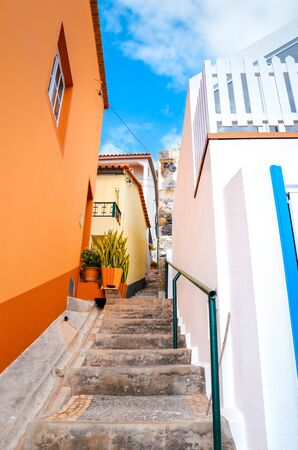 Beautiful narrow cobbled street in Jardim do Mar, Madeira Island, Portugal. Stone staircase along with colorful buildings. Orange and white facade. Mediterranean style. Summer vacation destination.
