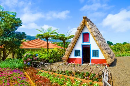Old traditional houses in Santana, Madeira Island, Portugal. Wooden, small, triangular and colorful houses represent a part of Madeira heritage. Surrounded by flowers. Tourist attraction.