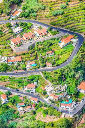 Aerial view of a village Curral das Freiras, Madeira Island, Portugal. Countryside houses, green terraced fields, and scenic serpentine road photographed from above. Aerial landscape. Travel spot. Stockfoto