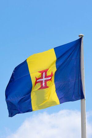 Waving flag of Madeira with blue sky in the background. It consists of a blue-yellow-blue vertical triband with a red-bordered white Cross of Christ in the center. Portuguese island in Atlantic ocean. Imagens