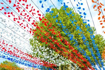 Piękne kolorowe dekoracje uliczne w Loreto, Madera, Portugalia. Obchody święta religijnego. Czerwone, białe, niebieskie i pomarańczowe papierowe kwiaty wiszą w powietrzu. Zielone drzewo w tle.
