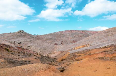 Volcanic landscape in Ponta de Sao Lourenco, Madeira, Portugal. Peninsula, easternmost point of the Portuguese island. Volcanic soil. Hilly terrain. Hikers on a trail in background. Tourist places. 版權商用圖片