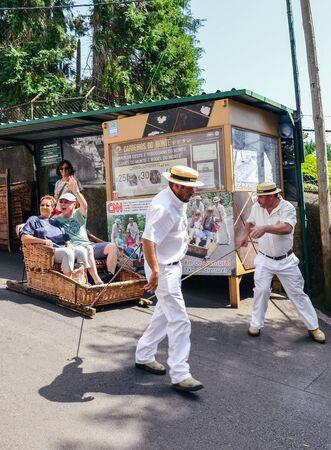 Monte, Madeira, Portugal - Sep 14, 2019 : les conducteurs de traîneaux à panier en osier, Carreiros do Monte, conduisent les gens en descente. Moyen de transport historique, maintenant une attraction touristique. Chapeau de paille typique.
