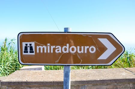 Old, partly damaged brown tourist sign saying miradouro in Portuguese. Information signs. Marking system. Arrow with a symbol of binocular. TRANSLATION: miradouro means viewpoint. Stok Fotoğraf