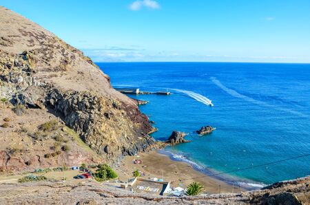 Beautiful Prainha Beach by the Atlantic Ocean in Madeira, Portugal. Surrounded by volcanic landscape and cliffs, people on the beach, sunny day. SIGN TRANSLATION: Prainha - small beach in Portuguese.