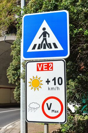 Road signs in Portuguese island Madeira. Blue zebra crossing sign. White speed limit sign. The speed restriction is dependent on weather, in case of clear weather the limit is plus 10 kmh than stated. Фото со стока