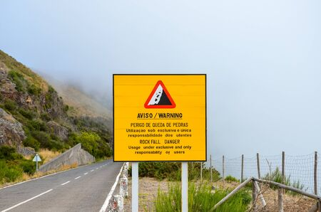 Yellow information sign warning of rockfall danger in Portuguese and English language. The usage of the road is under exclusive and only responsibility of the users. Misty landscape in the background.