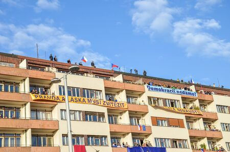 Prague, Czech Republic - Nov 16, 2019: People on balconies and on the roof supporting protests against Prime Minister Babis and Minister of Justice on Letna, Letenska plan. Banners, flags. 報道画像