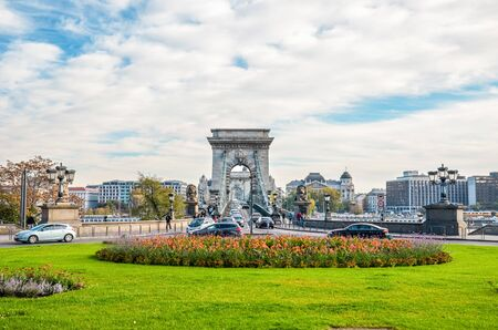 Budapest, Hungary - Nov 6, 2019: Szechenyi Chain Bridge in Budapest photographed with the adjacent roundabout leading to the famous landmark. Cars, traffic. Grass and flowers in the foreground.