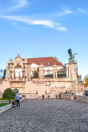 Budapest, Hungary - Nov 6, 2019: Historical courtyard of the Buda Castle. Statue of the mythological bird Turul and historical staircase in the background. Tourist attraction, people on the square.