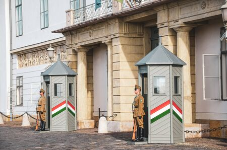 Budapest, Hungary - Nov 6, 2019: Castle guards in front of the Hungarian Presidential Palace, Sandor Palace. Armed presidential guards in uniform standing in front of the building. Honor guards.