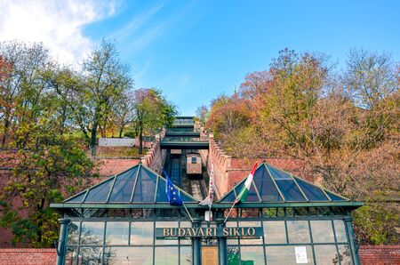 Budapest, Hungary - Nov 6, 2019: Cable car, public funicular train leading to the Buda Castle on the hill in the Hungarian capital. Tram tracks in the narrow corridor leading uphill. Transportation.