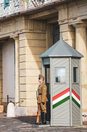 Budapest, Hungary - Nov 6, 2019: Castle guard in front of the Hungarian Presidential Palace, Sandor Palace. Armed presidential guard in uniform standing in front of the building. Honor guards.
