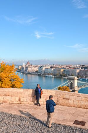 Budapest, Hungary - Nov 6, 2019: Asian man taking travel photo of his wife on the viewpoint above the Hungarian capital city. Danube river and Hungarian parliament building in the background.